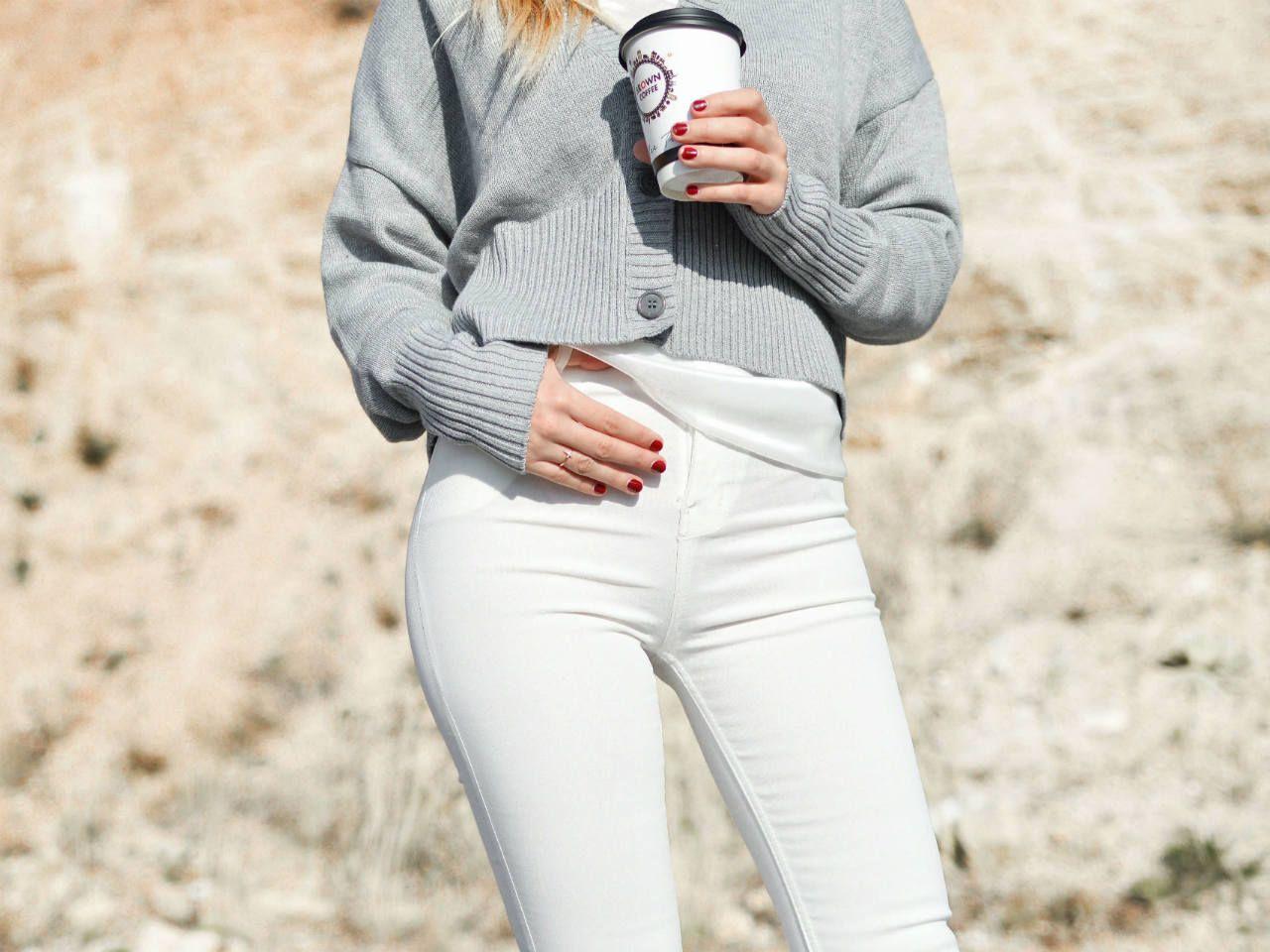 Beżowa bluza z kaputrem, jasne jeansy i białe trampki